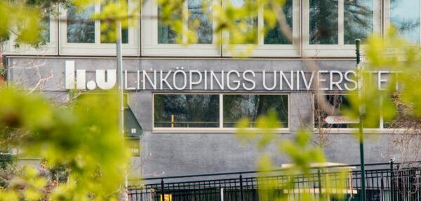Linköping Universitets logga på en husvägg med gröna löv i förgrunden